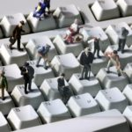 "GERMANY, Bonn, ""Online"" - Human miniatures on a computer keyboard."